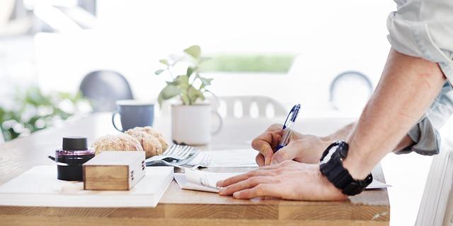 デスクで書類(申請書)を書いている男性