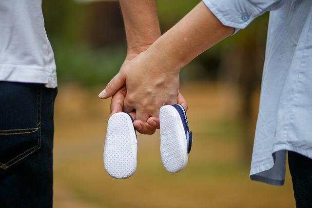 妊娠した女性、夫婦で手を繋ぐ、子どもの靴