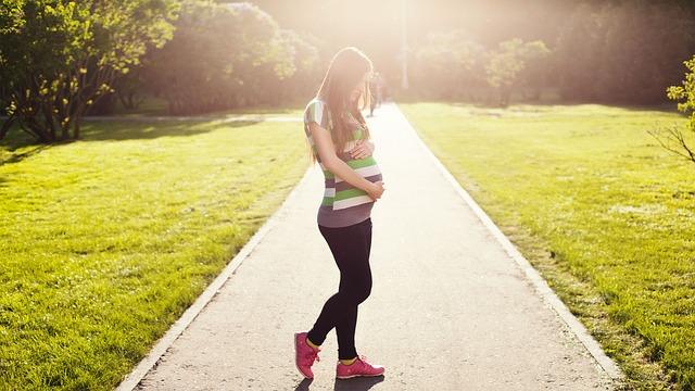 妊娠中の女性、草原、お腹を抑えてる女性