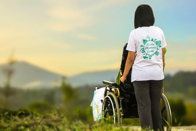 車いすに乗っている高齢者を介護している女性